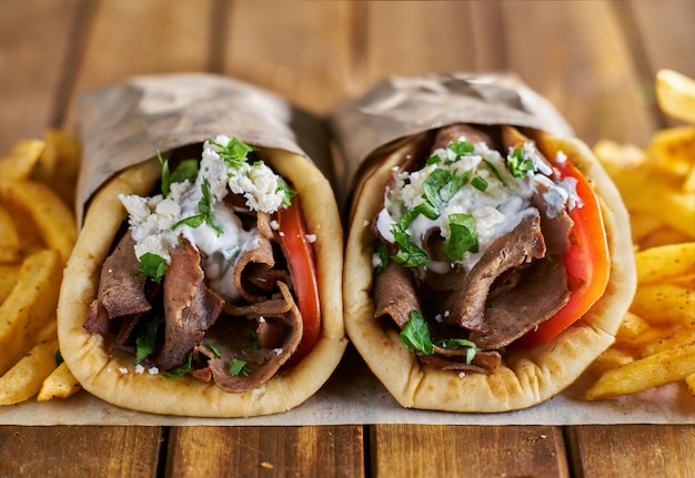 Two greek gyros with seasoned fries on wax paper