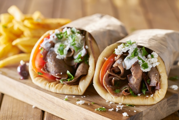 Two greek gyros with shaved lamb and french fries