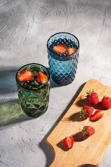 Две зеленые и синие геометрические стеклянные чашки с пресной водой и плодами клубники с красочными теневыми световыми лучами рядом с деревянной разделочной доской на каменно-бетонном фоне, угловой вид