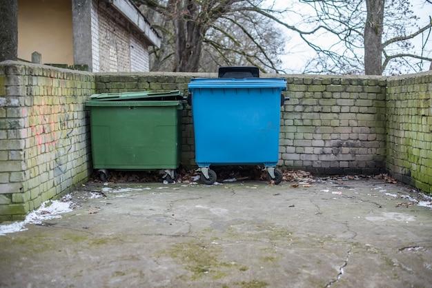 Два зеленых и синих контейнера для вторсырья снаружи, латвия