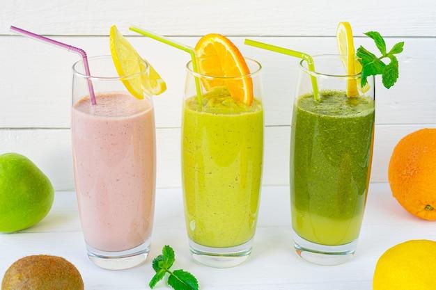 白い背景の上のストローとガラスのカップに2つの緑と1つのピンクのフルーツスムージー。水平方向高品質の写真