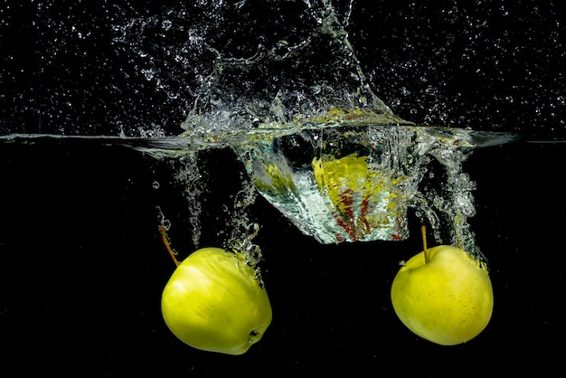 Two green apple splashing in water against black background