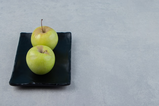 Due mele verdi su banda nera