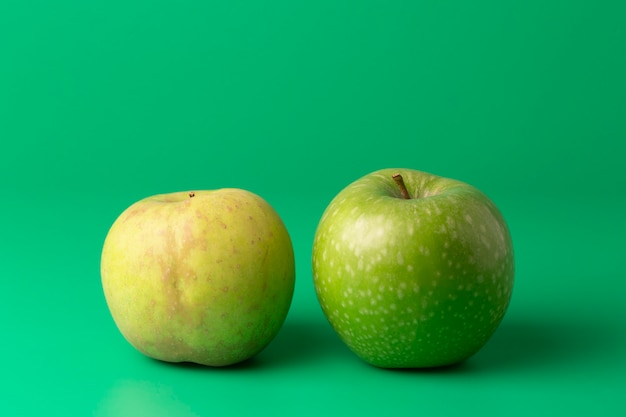 Two green apples on a green vertical