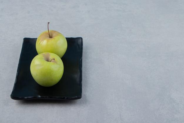 검은 접시에 두 개의 녹색 사과