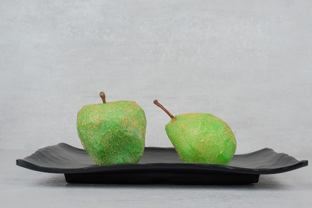 Two green apples with glitter on black plate.