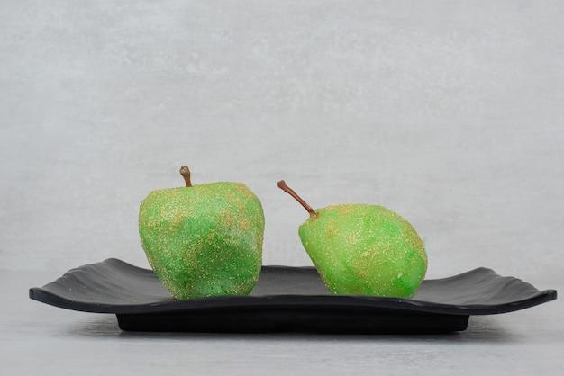Два зеленых яблока с блеском на черной тарелке.