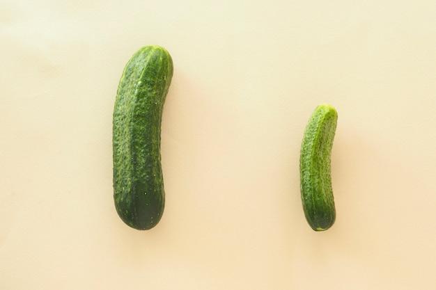 Два зеленых огурца на бежевом фоне. понятие о разных размерах мужского пениса.
