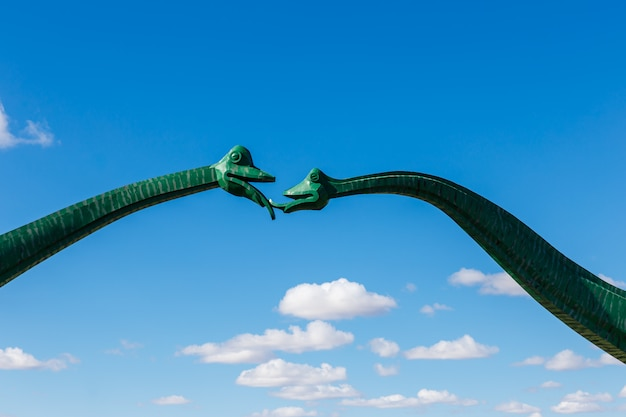 Two green dinosaurs kissing against a blue sky