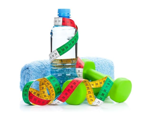 Две зеленые гантели, рулетка и бутылка для питья. фитнес и здоровье. изолированные на белом фоне