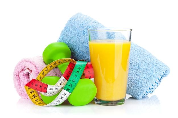 두 개의 녹색 아령, 줄자 및 오렌지 주스. 피트니스 및 건강. 흰색 배경에 고립