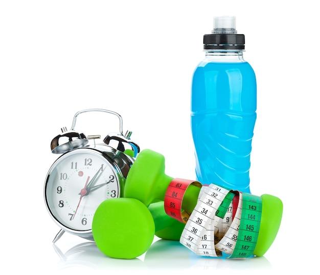 두 개의 녹색 덤벨, 줄자, 음료수 병 및 알람 시계. 피트니스 및 건강. 흰색 배경에 고립