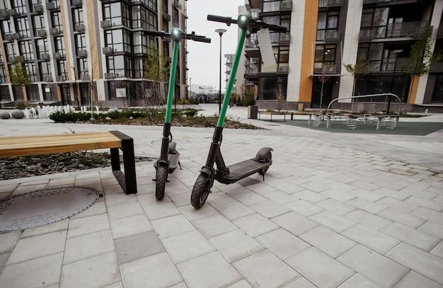 2つの緑の電動スクーター。街を旅する快適な方法。高速旅行のコンセプト。外に立っている公共のシェアのための電動スクーター。エコトランスポートのコンセプト。