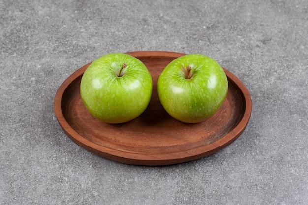 Due mele fresche verdi sul bordo di legno della cucina