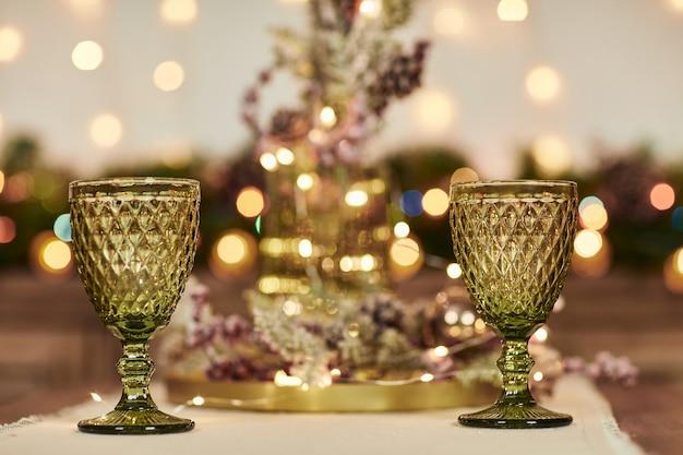 木製のテーブルに2つの緑色のグラス。クリスマスの飾り