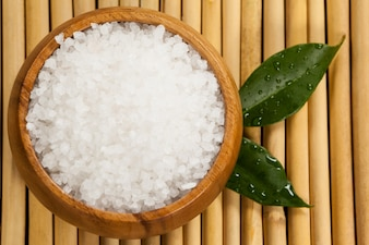 Two green leaves and sea salt in wooden bowl