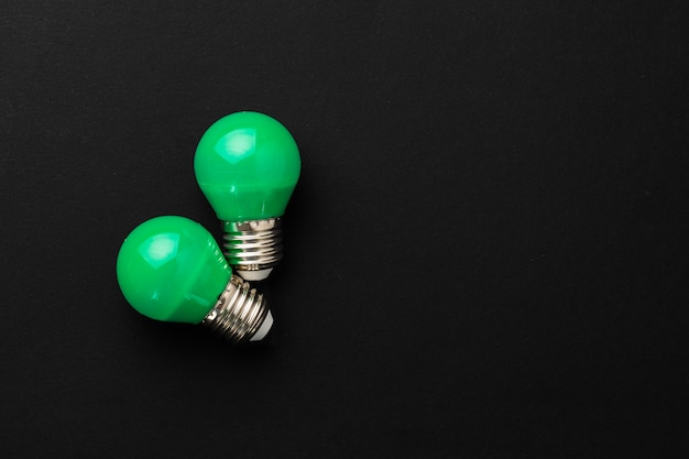 Two green light bulbs on black surface