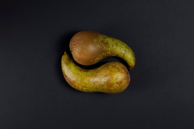 2つの緑の梨は陰陽のシンボルの形で横たわっています。