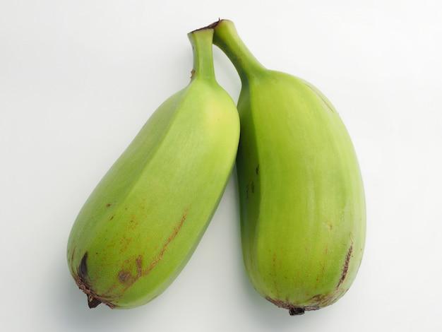 Два зеленых бананов на белом фоне