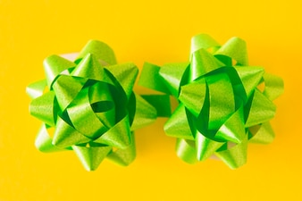 Two green satin ribbon bows on yellow background