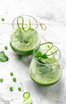 白い背景、垂直方向の画像に新鮮なエンドウ豆、キュウリ、ほうれん草、ライムと2つの緑のスムージー。上面図。