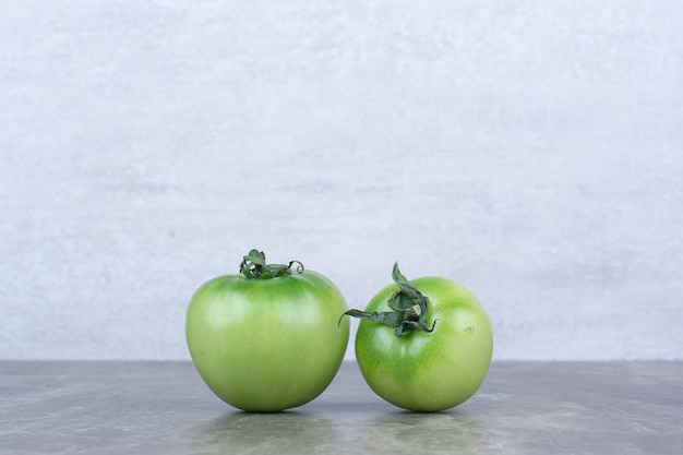 Two green tomatoes on marble table.