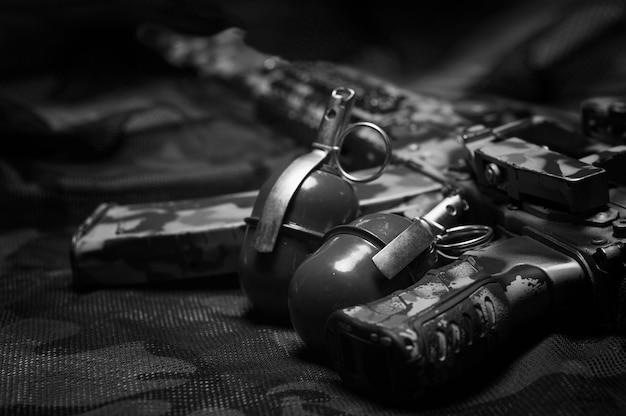 Две гранаты лежат на камуфляжном фоне. понятие о военных действиях, политических конфликтах, вооруженных силах. вид сверху. смешанная техника