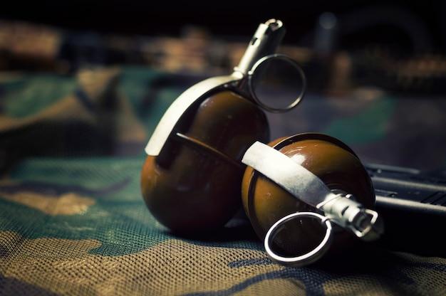 Две гранаты лежат на камуфляжном фоне. понятие о военных действиях, политических конфликтах, вооруженных силах.