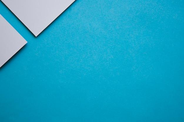 Due carte di cartone grigio all'angolo dello sfondo blu