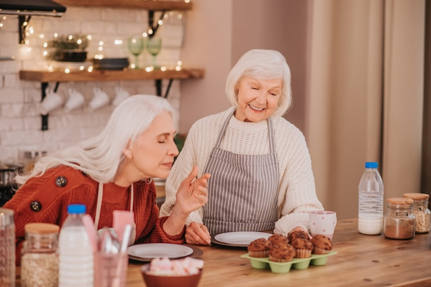 モダンなキッチンで料理を楽しむ2人の白髪の女性
