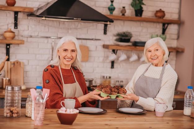 モダンなキッチンに座っている2人の白髪の女性