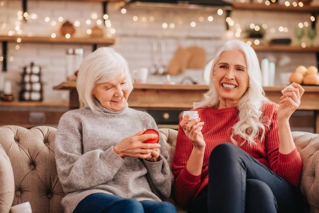 새로운 노화 방지 크림에 대해 논의하는 두 명의 회색 머리의 즐거운 귀여운 숙녀