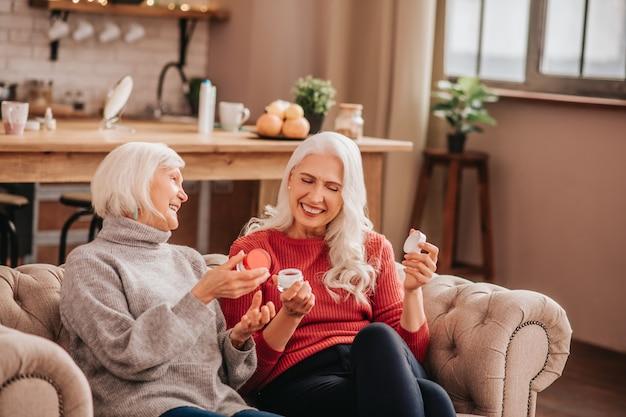 새로운 노화 방지 크림에 대해 이야기하는 두 명의 회색 머리의 즐거운 귀여운 숙녀
