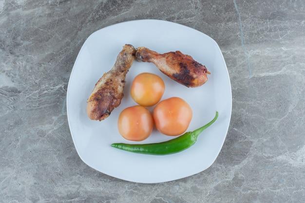 Две куриные голени на гриле с помидорами и перцем.