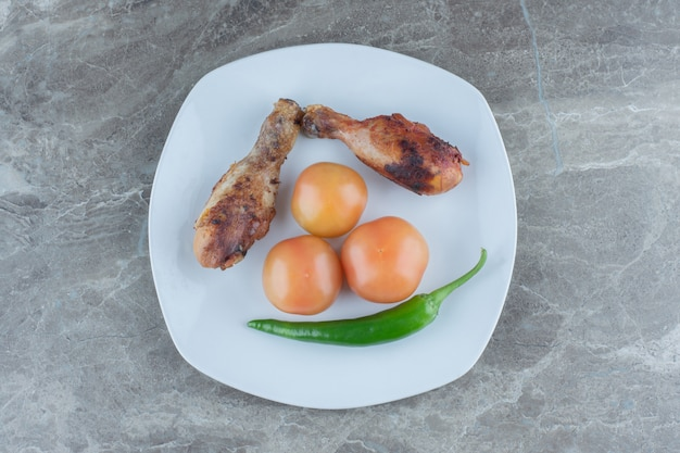 Due cosce di pollo alla griglia con pomodoro e pepe.