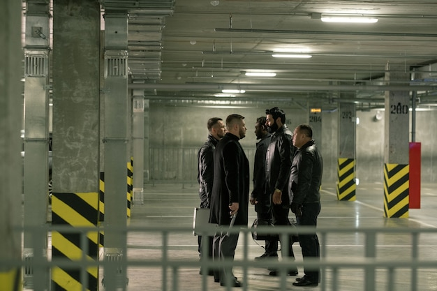 Two groups of intercultrual men with handguns interacting while standing in front of each other on parking area