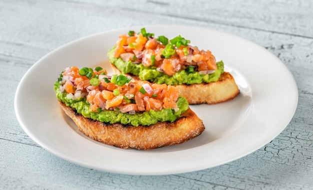 Two guacamole and salmon toasts on white plate