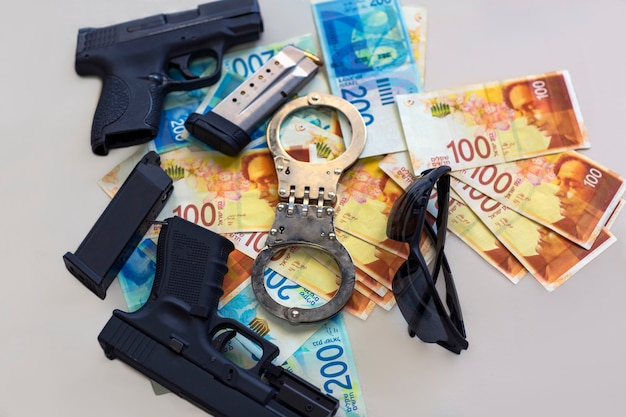 두 개의 총, 수갑, 이스라엘 새 셰켈 지폐. 탄창이 있는 반자동 권총 총기