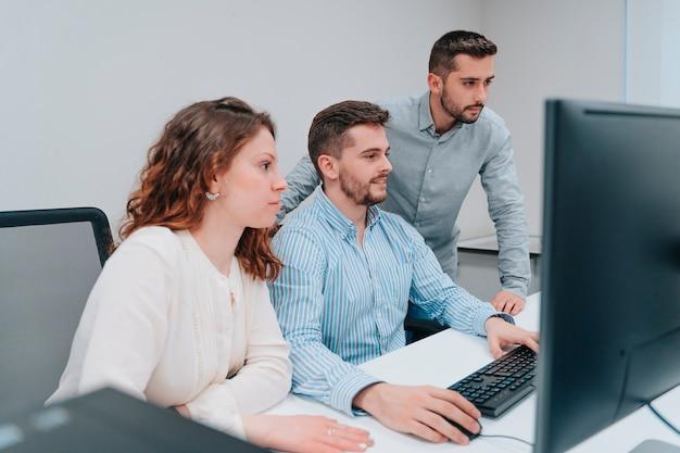 두 남자와 여자 동료가 문제를 해결하는 동안 컴퓨터를보고