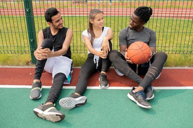 Два парня и девушка в спортивной одежде болтают, сидя на детской площадке или баскетбольной площадке у сетки