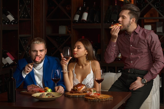 Two guys eagerly eat food in a restaurant, and a girl with a glass of red wine misses, in a restaurant