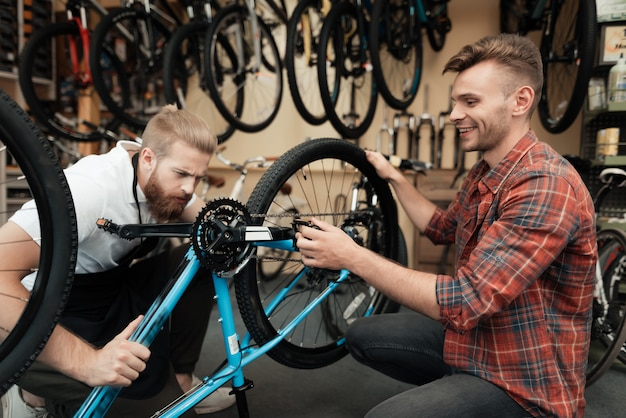 Two guys examine bicycle in sport workshop