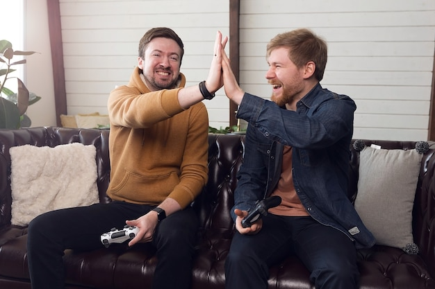 Два друга парня играют в игровую консоль, игры и развлечения дома. фото высокого качества