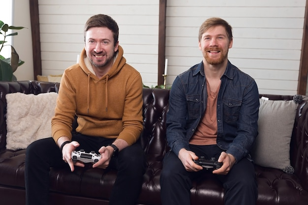 집에서 게임 콘솔, 게임 및 엔터테인먼트를하는 두 남자 친구. 고품질 사진