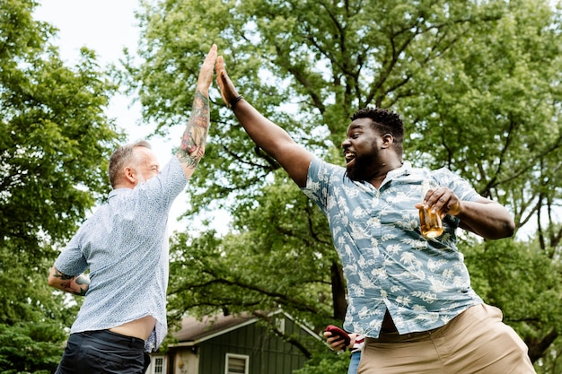 Two guys giving each other a high five at a summer party