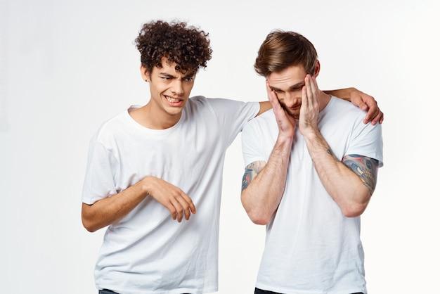 友情のコミュニケーションの感情の横にある白いtシャツを着た2人の男。高品質の写真