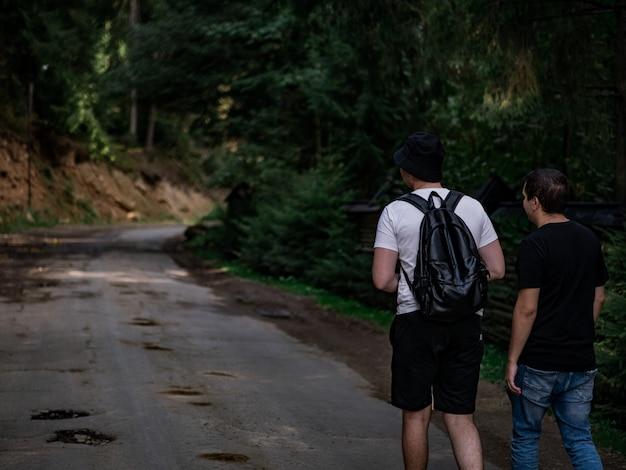 黒のtシャツと白のtシャツを着た2人の男が、林道を歩いています。