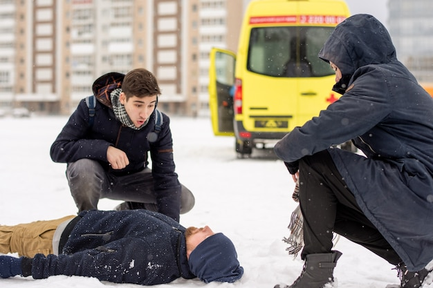 雪の中で横たわっている病気または無意識の若い男によってスクワットに座っている2人の男