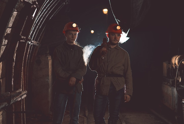 Two guys in special clothes and helmets standing in the mine. miners