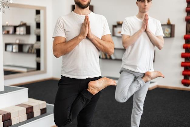 두 남자가 한쪽 다리로 서서 피트니스 수업에서 명상을 합니다. 젊은 남자들이 요가 포즈를 연습합니다.